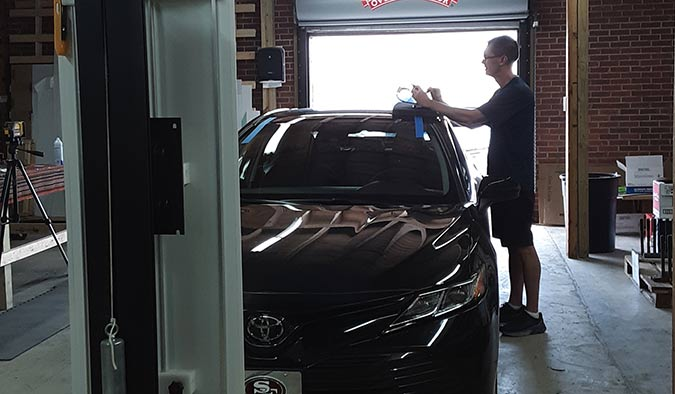 An A Glass technician performing a car windshield recalibration for a client's car in Florence.